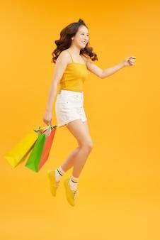 Привлекательная счастливая женщина прыгает бежать держа хозяйственные сумки над оранжевым фоном. летняя концепция