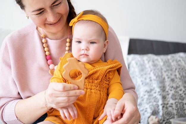 魅力的な幸せな女性は彼女の赤ん坊の娘と遊ぶ。女の赤ちゃんは木製の歯で遊ぶ。小さな子供のためのおもちゃ。初期の開発