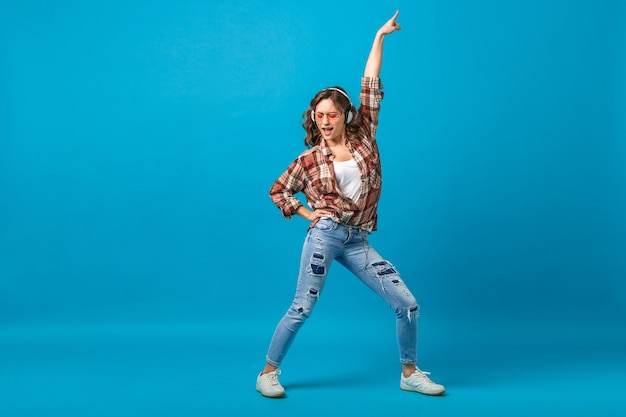 Attractive happy woman posing in cheerful mood listening to music in headphones in checkered shirt and jeans isolated on blue studio background, looking up