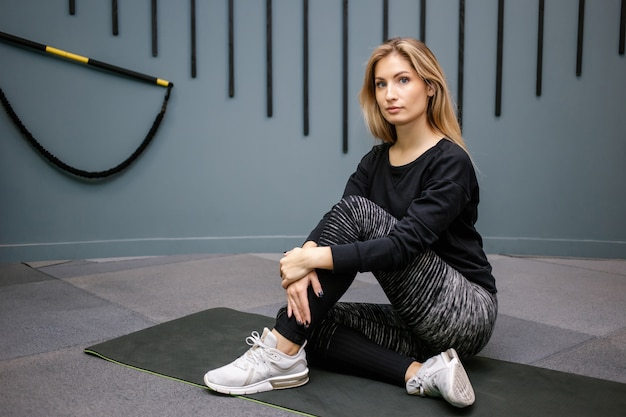 체육관 배경에 운동 후 바닥에 앉아 매력적인 행복 한 여자. 슬림하고 건강한 여자 운동의 개념.