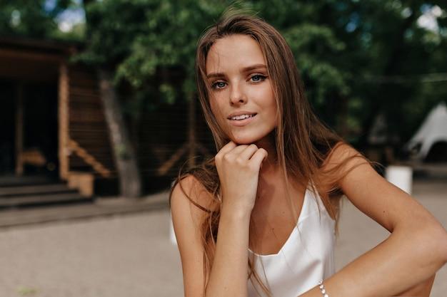 Attraente donna felice che indossa la maglietta bianca in spiaggia nella soleggiata giornata calda