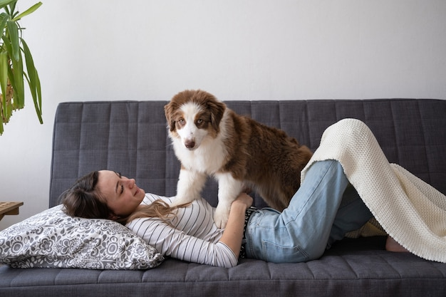 Привлекательная счастливая женщина с красивой маленькой милой австралийской овчарки красный трехцветный щенок, лежащий на диване. любовь и дружба между человеком и животным.