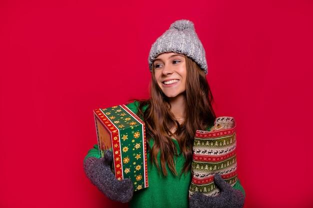 긴 밝은 갈색 머리와 멋진 미소를 가진 매력적인 행복한 여자 겨울 회색 모자, 장갑 및 새해 선물을 들고 격리 된 빨간색 배경에 웃고 녹색 스웨터를 입고