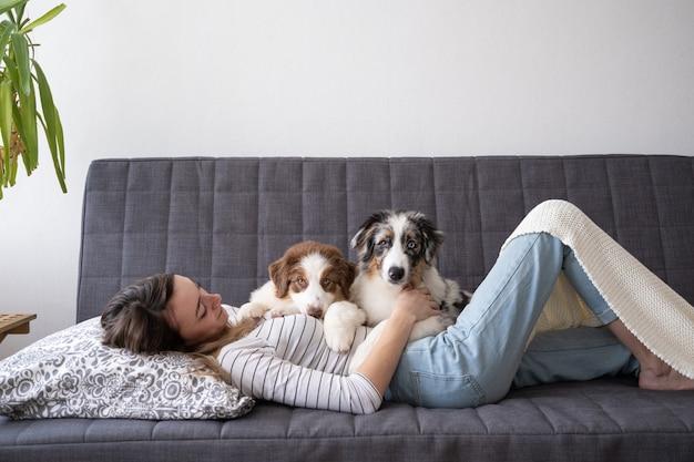 Привлекательная счастливая женщина с двумя красивыми маленькими милыми австралийскими овчарками, красный трехцветный щенок синего мерле, лежа на диване