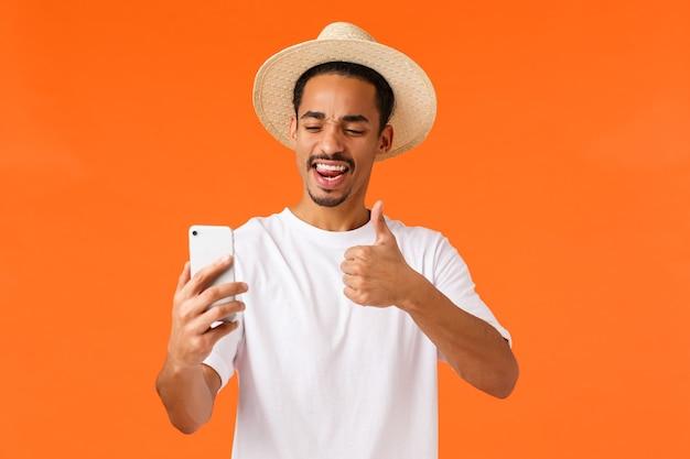 休暇中の魅力的な幸せな若いアフリカ系アメリカ人男性観光客、スマートフォンで自分撮りを取り、承認を示す、親指を立てる、生意気な舌を棒で喜ばせる表現、オレンジ色の背景