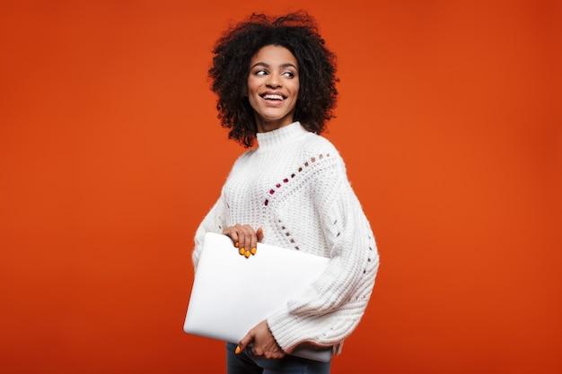 赤い壁の上に孤立して立って、ラップトップコンピューターを運ぶ魅力的な幸せな若いアフリカの女性