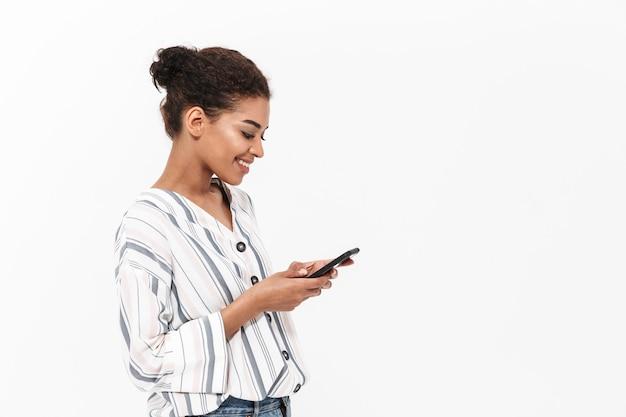 白い壁の上に孤立して立っているカジュアルな服を着て、携帯電話を使用して、祝う魅力的な幸せな若いアフリカの女性