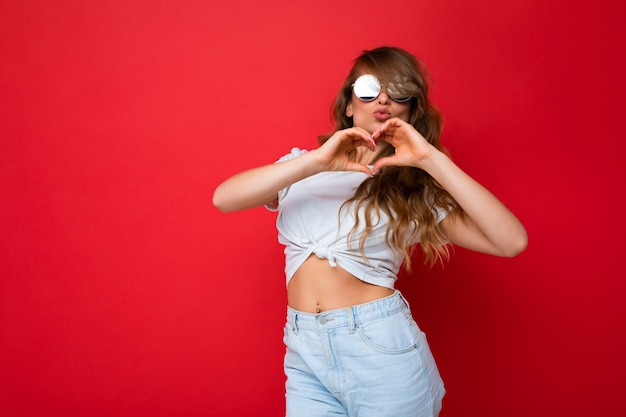 Attractive happy young blonde woman wearing everyday stylish clothes and modern sunglasses isolated on colorful background wall looking at camera and ahowing heart gesrure
