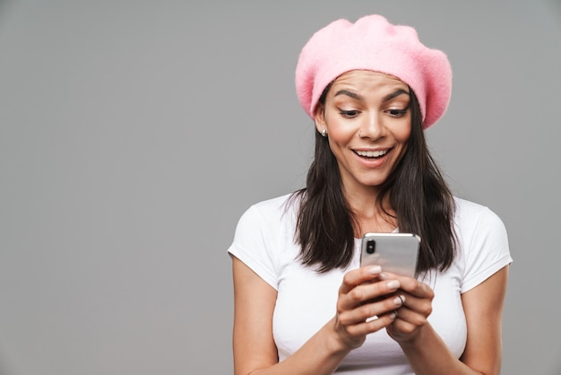 Attractive happy young brunette woman wearing beret standing isolated over gray wall, holding mobile phone