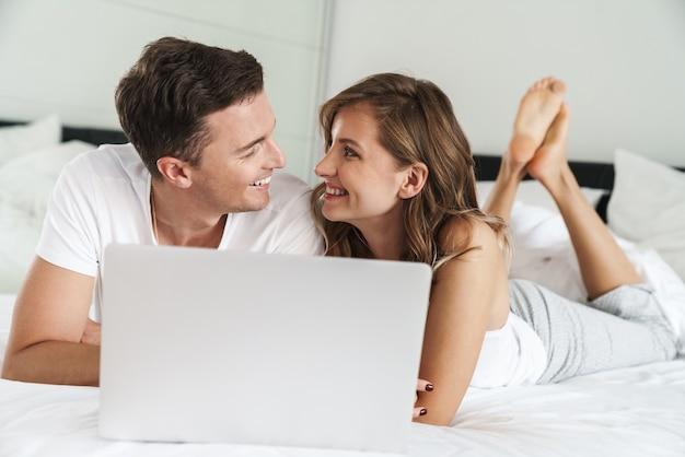 Привлекательная счастливая молодая пара, лежа на кровати в спальне дома, используя портативный компьютер