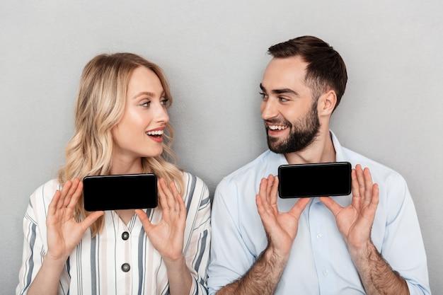 孤立して立っている魅力的な幸せな若いカップル、空白の画面の携帯電話を表示