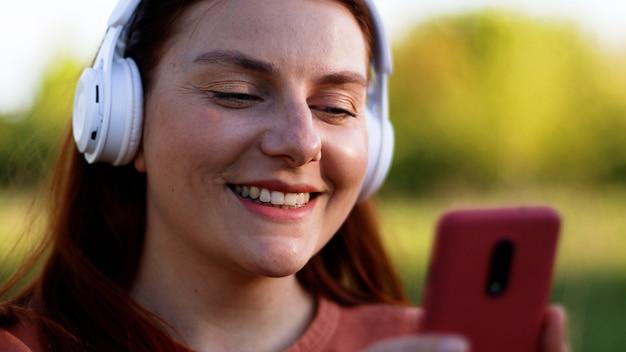 Привлекательный счастливый студент маленькой девочки, слушающий музыку с наушниками. студент с помощью мобильного телефона в чате.