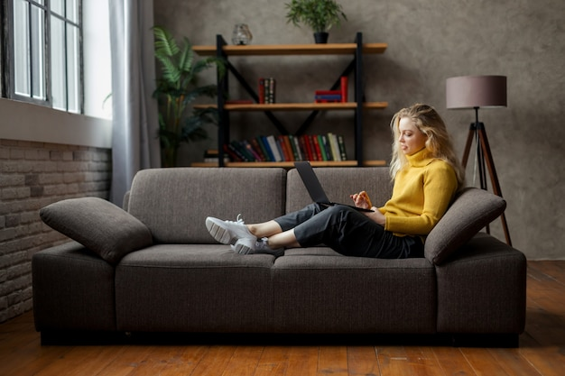 Студент привлекательной счастливой молодой девушки учится дома, лежа на диване и используя портативный компьютер