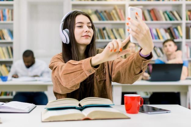 Привлекательный счастливый студент молодой девушки, одетый в повседневную одежду и наушники-хипстеры, сидит за столом с книгами, держит мобильный телефон для селфи фото