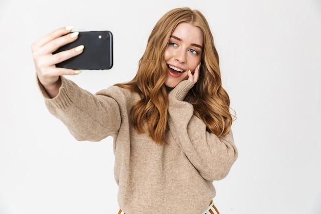 흰색 벽에 격리된 채 스웨터를 입고 셀카를 찍고 있는 매력적인 행복한 어린 소녀