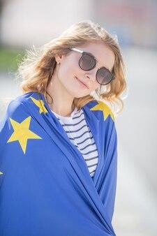 Привлекательная счастливая молодая девушка с флагом европейского союза.