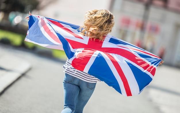 영국의 국기와 함께 매력적인 행복 한 어린 소녀.