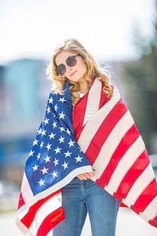 Привлекательная счастливая молодая девушка с флагом соединенных штатов америки.