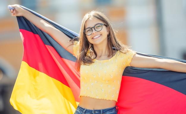 독일 국기와 함께 매력적인 행복 한 어린 소녀입니다.