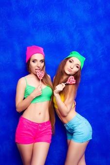 Привлекательные счастливые молодые подруги в кепках, держащих леденцы на палочке