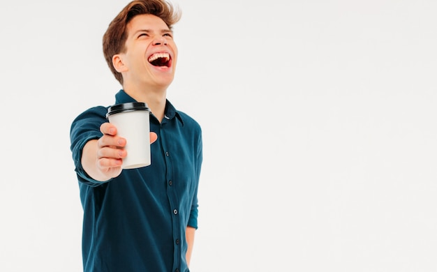 Attractive happy young man holding cup of coffee to go on white