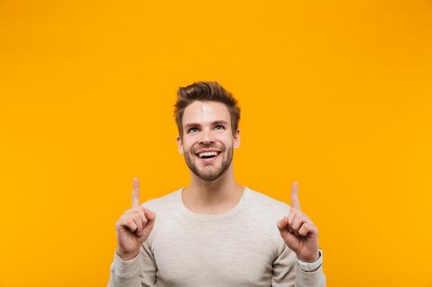 Привлекательный счастливый молодой человек в пуловере стоит изолированно над желтой стеной, представляя пространство для копирования