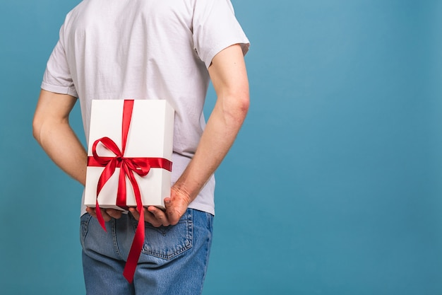 그의 생일 선물 상자를 들고 아름 다운 미소와 함께 매력적인 행복 한 젊은 남자
