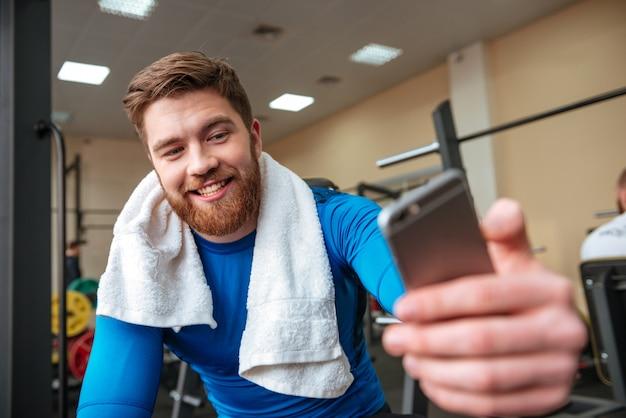 魅力的な幸せな若いスポーツマンは電話でselfieを作る。
