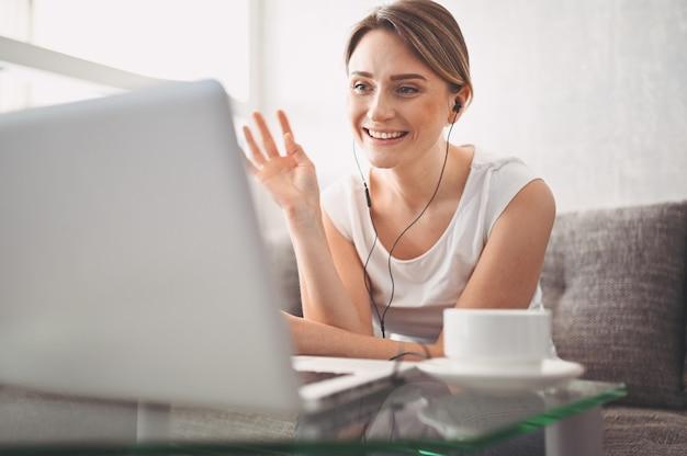 Привлекательный счастливый молодой студент, обучение в интернете на дому, используя портативный компьютер, наушники, видео чат, размахивая. удаленная работа, дистанционное обучение. видеоконференция или виртуальное мероприятие на карантине