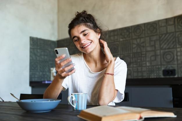 매력적인 행복 한 젊은 여자 집에서 부엌에서 건강한 아침 식사, 휴대 전화 메시징