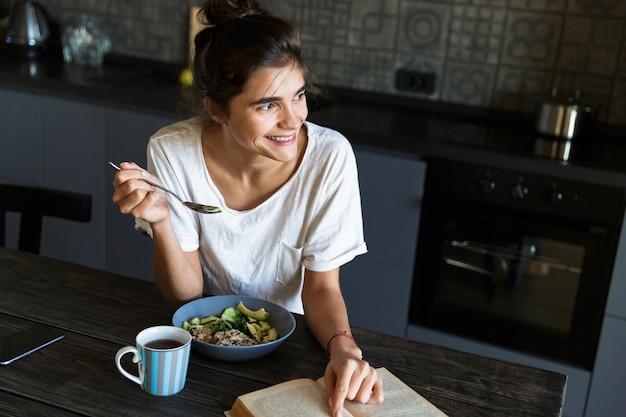 매력적인 행복 한 젊은 여자 집에서 부엌에서 건강한 아침 식사, 책을 읽고