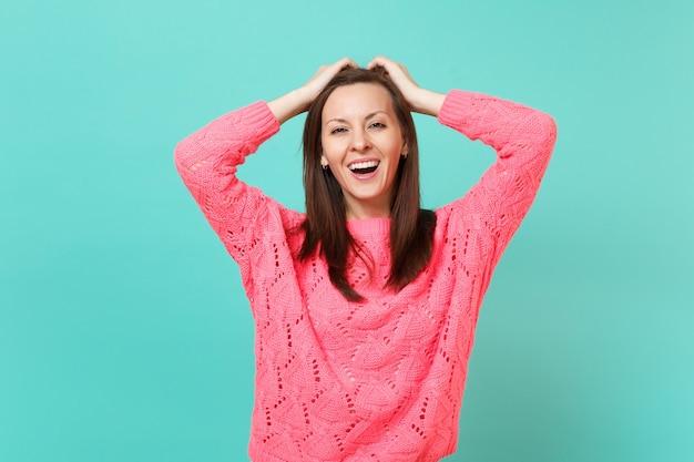 青いターコイズブルーの壁の背景、スタジオの肖像画に分離された頭に手を置くニットピンクのセーターの魅力的な幸せな若い女性。人々の誠実な感情、ライフスタイルのコンセプト。コピースペースをモックアップします。