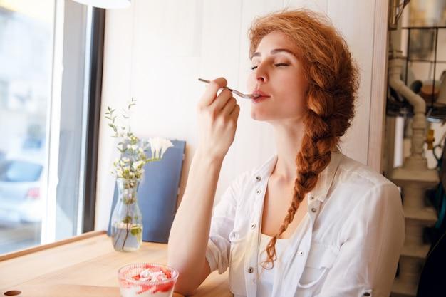 魅力的な幸せな若い女性に座って、デザートを食べてお楽しみください。