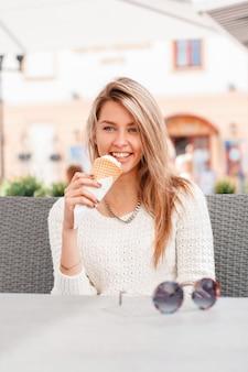 야외 카페에서 그녀의 손에 아이스크림 니트 흰색 스웨터에 달콤한 미소로 자연스러운 메이크업으로 아름 다운 파란 눈을 가진 매력적인 행복 한 젊은 여자. 매력적인 여자 모델.