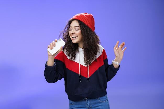 帽子をかぶった巻き毛の魅力的な幸せな若い女性は、スマートフォンで一緒に歌う完璧な冬の日を楽しんで、マイクのような携帯電話を持って、青い背景の上にカラオケを崇拝します。