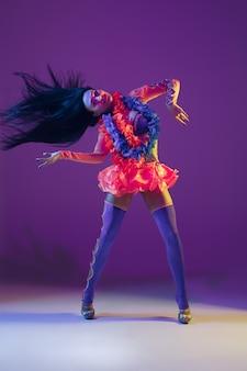Привлекательная гавайская модель брюнетки на фиолетовом фоне студии в неоновом свете