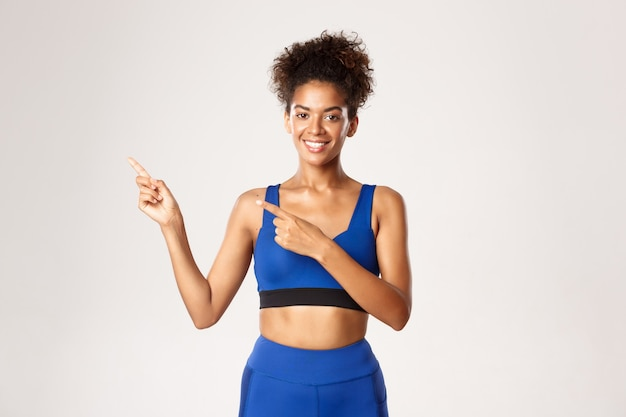 Attractive and healthy african-american fitness woman, wearing blue sport outfit, pointing fingers