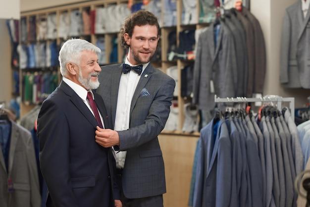 Привлекательный клиент помощи примеряя куртку в выставочной комнате.