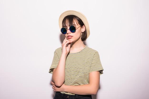 Ragazza teenager di moda attraente hipster in cappello, occhiali da sole nel muro bianco