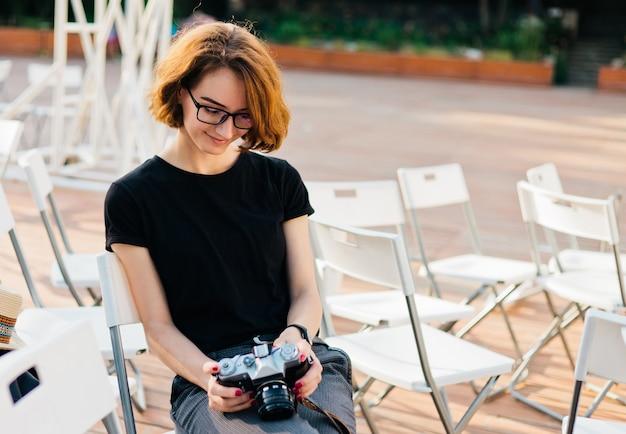 メガネで魅力的な内気な少女は、屋外の椅子に座っている間彼女の手でレトロなカメラを保持しています。