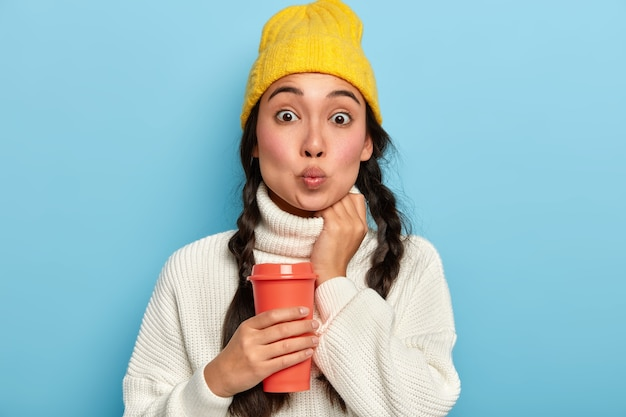 Attractive hipster girl with two pigtails keeps lips rounded, makes grimace at camera, dressed in warm winter sweater and stylish yellow hat,