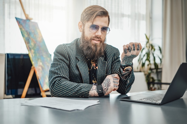 Привлекательный хипстерский парень с татуировками в костюме позирует, сидя за столом с ноутбуком в современной квартире. удаленная работа и домашний образ жизни.