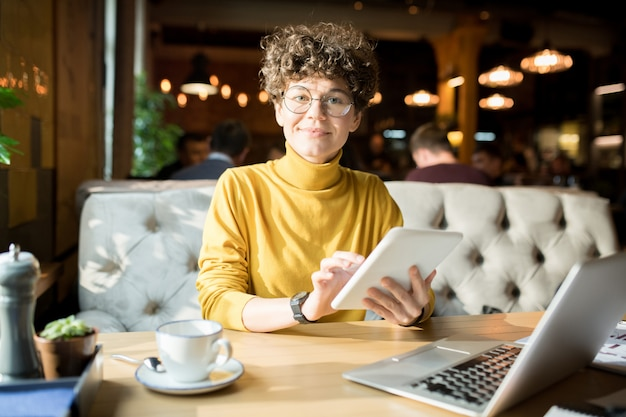 Attractive hipster lady working with tablet in restaurant