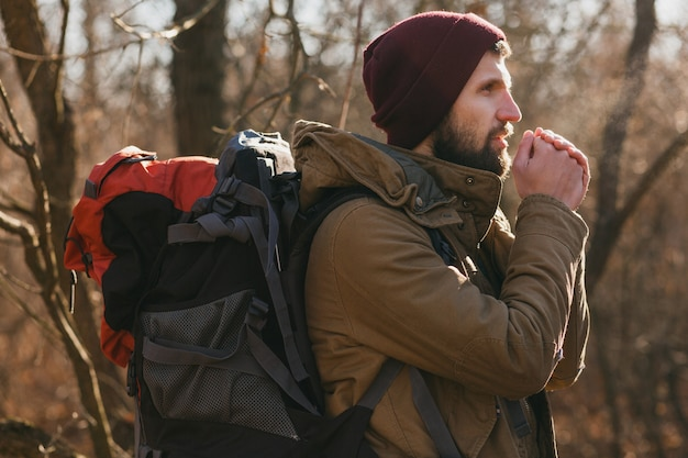 Attractive hipster man traveling with backpack in autumn forest wearing warm jacket and hat, active tourist, exploring nature in cold season