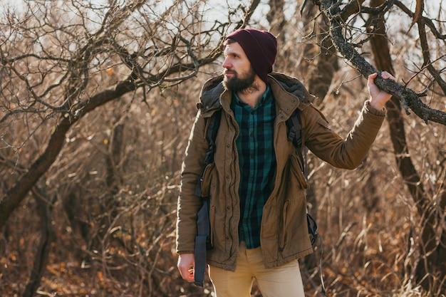 Uomo attraente hipster che viaggia con lo zaino nella foresta di autunno che indossa giacca calda e cappello, turista attivo, esplorando la natura nella stagione fredda