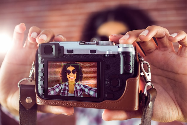 Attractive hipster taking selfies with camera
