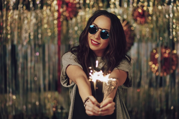 Attractive hipster woman holding sparklers in hands