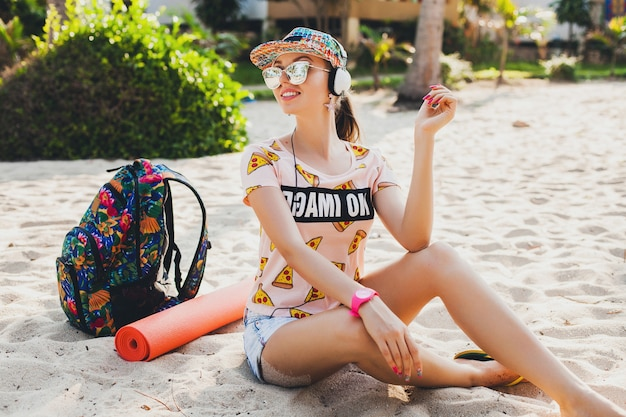 アクセサリーキャップサングラスを身に着けている、スタイリッシュなカラフルな衣装でヘッドフォンで音楽を聴いてビーチに座っている魅力的な流行に敏感な女性、バックパックと一緒に旅行を笑顔