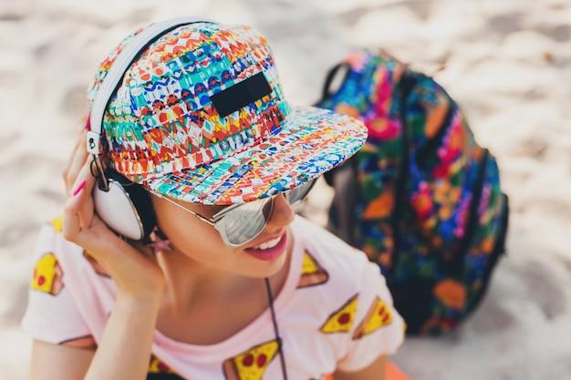 アクセサリーキャップサングラスを身に着けているスタイリッシュなカラフルな衣装でヘッドフォンで音楽を聴いてビーチを歩いている魅力的な流行に敏感な女性、バックパックと一緒に旅行を笑顔