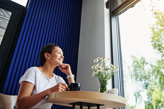 コーヒーブレイクを楽しんでコーヒーを飲みながらカフェテリアでリラックスする魅力的なヒスパニック系女性